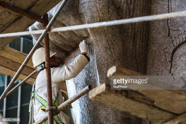 Egyptian workers restore a giant granite statue of the ancient Egyptian Pharaoh Ramses II at the Atrium of the Grand Egyptian Museum , near the...