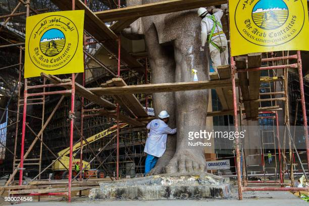 Egyptian workers restore a giant granite statue of the ancient Egyptian Pharaoh Ramses II at the Atrium of the Grand Egyptian Museum near the...