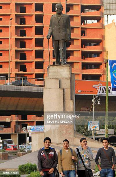 Egyptian youth stand under a statue of Egyptian novelist Naguib Mahfouz in Cairo on December 11 2011 as a patch covers his eye in a symbolic tribute...