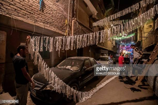Egyptian youths decorate their residential street in preparation for the Muslim holy month of Ramadan in Cairo's Hadayek el-Maadi district, on April...