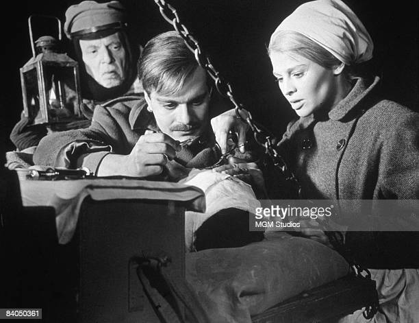 Egyptianborn actor Omar Sharif and British actress Julie Christie stitch up a man in bandages in a still from the film 'Doctor Zhivago' directed by...