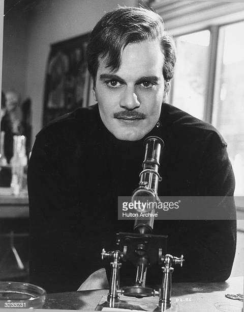 Egyptianborn actor Omar Sharif sitting next to a microscope in a promotional portrait for director David Lean's film 'Doctor Zhivago'