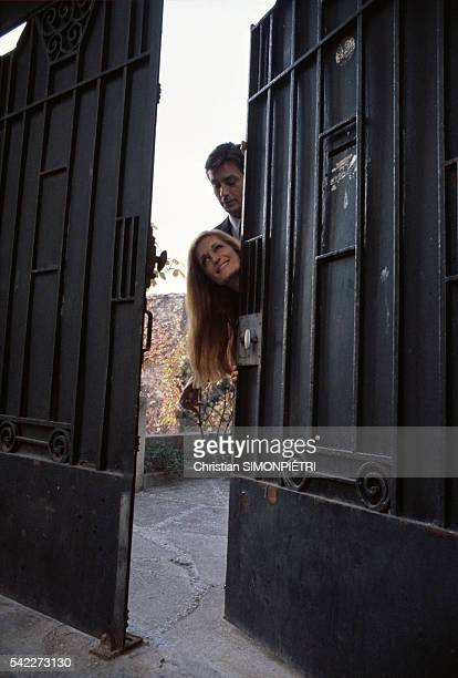 Egyptianborn Italian singer Dalida and French actor Alain Delon stand behind a courtyard door during the music video shoot for their duet 'Paroles...