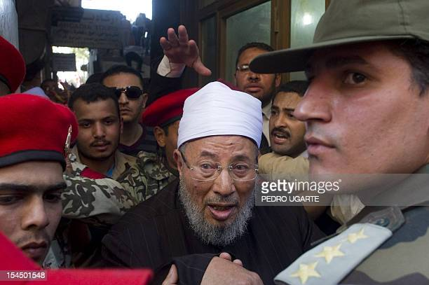 Egyptianborn Muslim cleric Sheikh Yussef alQaradawi is escorted by a soldier as he leaves Cairo's central Tahrir square on February 18 2011 where he...