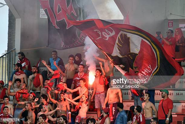 Egyptian's Al Haly supporters wave and light flares in the tribune on November 29 2014 at Robert Champroux stadium in Abidjan during their...