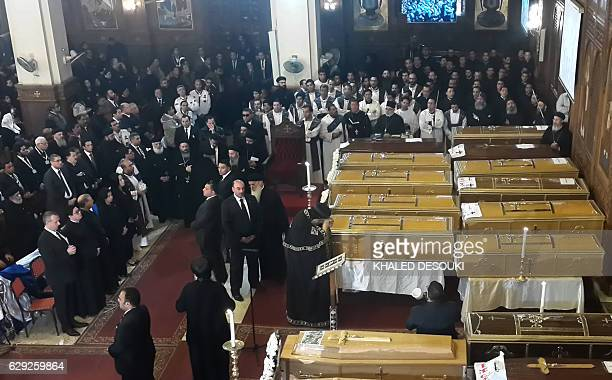 Egyptians and clergymen stand next to the coffins of the victims of a bomb explosion that targeted a Coptic Orthodox Church the previous day in Cairo...