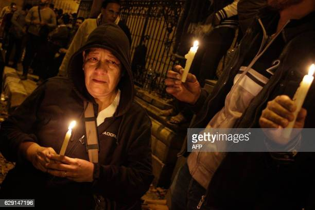 Egyptians carry candles during a vigil for the victims of a bomb explosion that targeted the Saint Peter and Saint Paul Coptic Orthodox Church on...