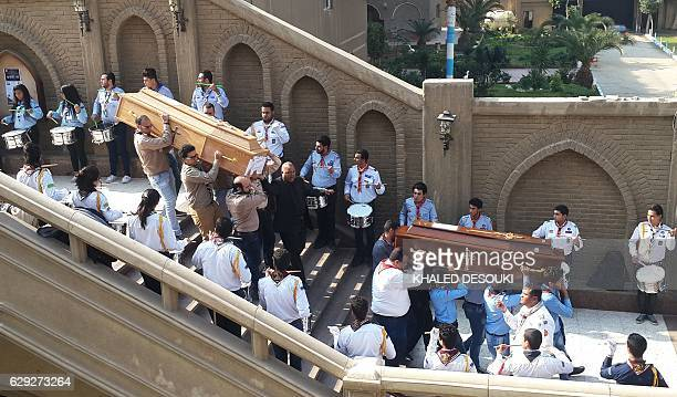Egyptians carry the coffins of the victims of a bomb explosion that targeted a Coptic Orthodox Church the previous day in Cairo at the end their...