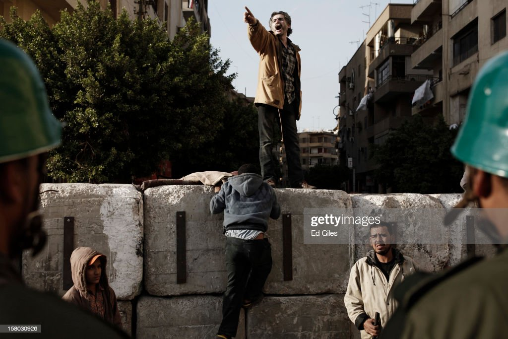 Egyptians climb a concrete wall recently built near Egypt's Presidential Palace during a demonstration against Egyptian President Mohammed Morsi on December 9, 2012 in Cairo, Egypt. Anti-Morsi protesters continue to demonstrate across Egypt against the country's draft constitution, rushed through parliament in an overnight session on November 29. The country's new draft constitution, passed by a constitutional assembly dominated by Islamists, will go to a referendum on December 15. (Photo by Ed Giles/Getty Images).