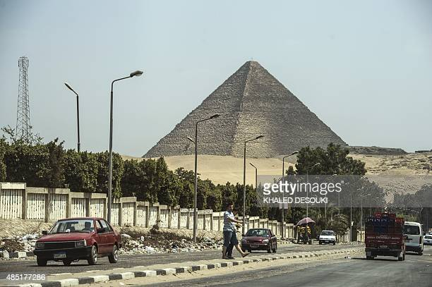 Egyptians cross a road in front of the Great Pyramid of Cheops also known as Pyramid of Khufu in south Cairo's Giza district on August 25 2015 The...