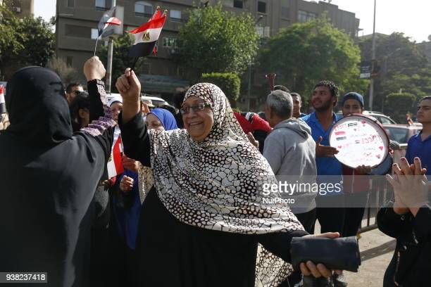 Egyptians dance and celebrate with national flags as some wear tshirts depicting incumbent President Abdel Fattah alSisi outside a polling station in...