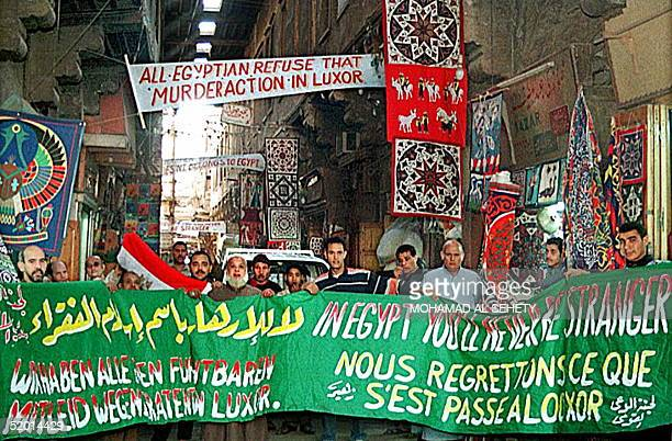 Egyptians display a banner at a souk in Cairo 03 December bearing slogans to reassure and apologize to tourists after the massacre of 58...