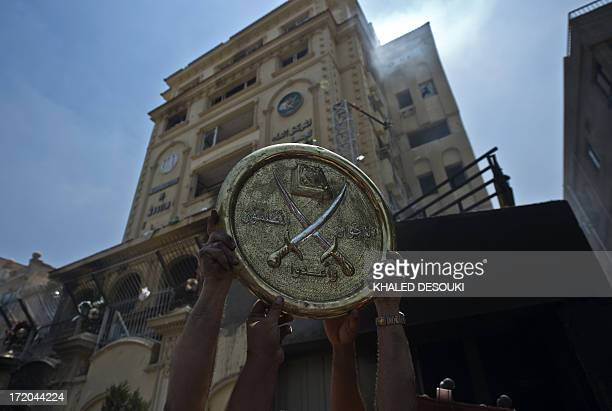 Egyptians hold a plaque of the Muslim Brotherhood emblem which was removed from the party's burnt headquarters in the Moqattam district of Cairo on...