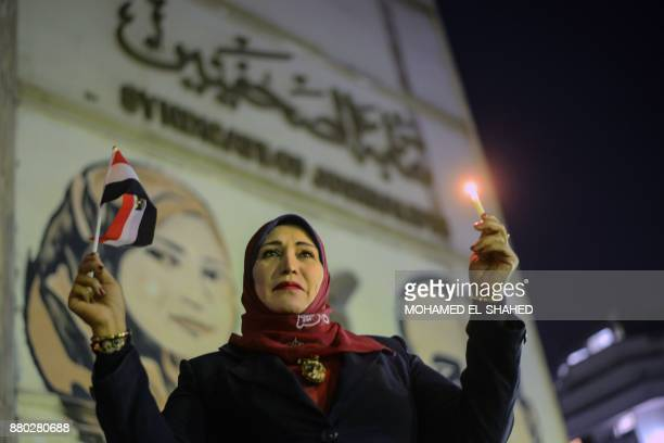 Egyptians hold candles at a vigil outside the Syndicate of Journalists in the capital Cairo's downtown district on November 27 in the memory of the...