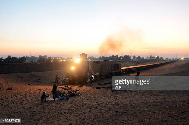 Egyptians inspect the site of an accident near a railway crossing where a train ploughed into a truck and the minibus on November 18 2013 in Dahshur...