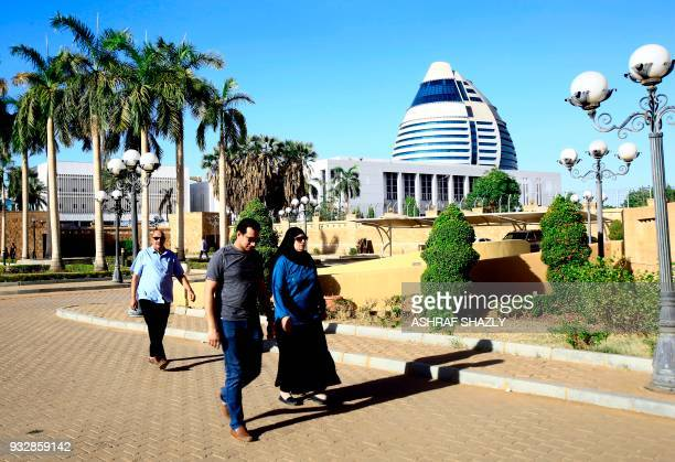 Egyptians living in Sudan walk near the Burj AlFateh hotel on the banks of the Nile river as they arrive at the Egyptian embassy in Khartoum on March...