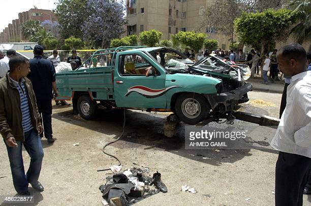 Egyptians look at a destroyed police vehicle following an attack which targeted and killed senior police officer Brigadir General Ahmed Zaki after an...
