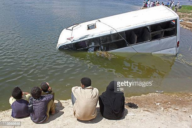 Egyptians look at a sunken minibus in which twentytwo people drowned when it fell into the Nile River in the southern Egyptian town of Beni Suef 110...