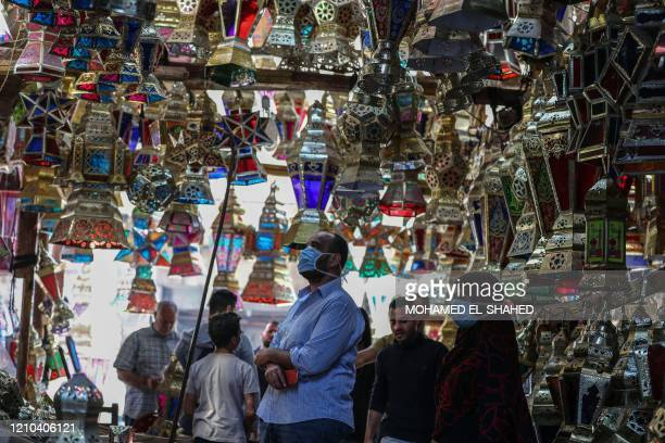 "Egyptians look at traditional lanterns known in Arabic as ""Fanous"" sold during the Muslim holy month of Ramadan in Cairo's Sayeda Zainab..."