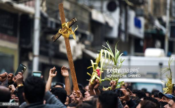 Egyptians raise a wooden cross and palm leaves originally intended for Palm Sunday celebrations as they gather outside the Coptic Orthodox...