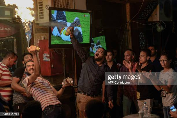 Egyptians react as they watch the FIFA World Cup 2018 qualification football match between Egypt and Uganda at a café in Cairo's 6th of October City...