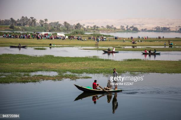 Egyptians ride boats along one of the branches of the Nile in the southern town of Mallawi on April 9 as they celebrate Sham alNessim a Pharaonic...