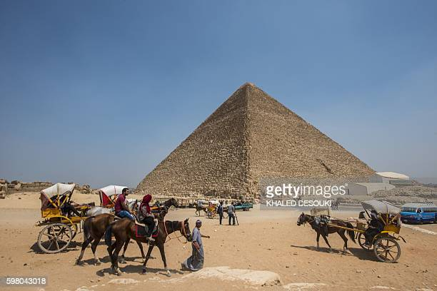 Egyptians ride their carts past the Great Pyramid of Cheops aka Pyramid of Khufu on August 31 2016 on the Giza Plateau on the southern outskirts of...