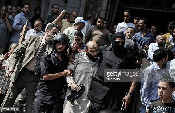 Egyptians security forces escort an Islamist supporter of the Muslim Brotherhood out of the al-Fatah mosque, in downtown Cairo, Egypt, on August 17,...