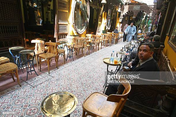 Egyptians sit at the popular ElFishawi coffee shop in the usually busy Khan alKhalili bazaar in Cairo on February 23 the scene of a deadly bomb blast...