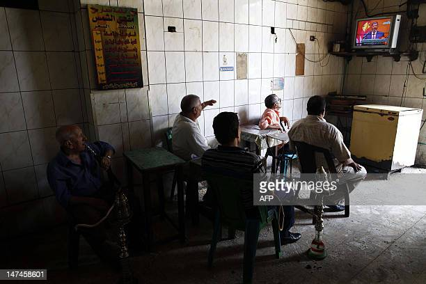 Egyptians sitting in a traditional coffee shop watch on TV President Mohamed Morsi take the oath of office in Cairo on June 30, 2012 to become...