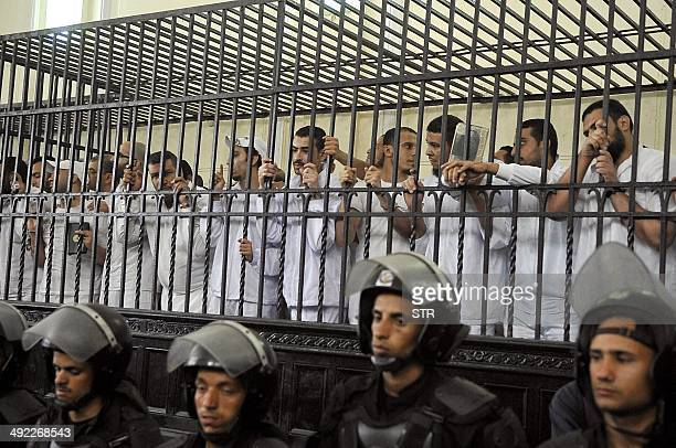 Egyptians stand behind the defendants cage on May 19 2014 during their trial over deadly violence in the Sidi Gaber neighbourhood of the northern...