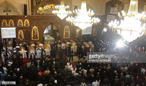 Egyptians stand next to the coffins of the victims of a bomb explosion that targeted a Coptic Orthodox Church the previous day in Cairo during their...