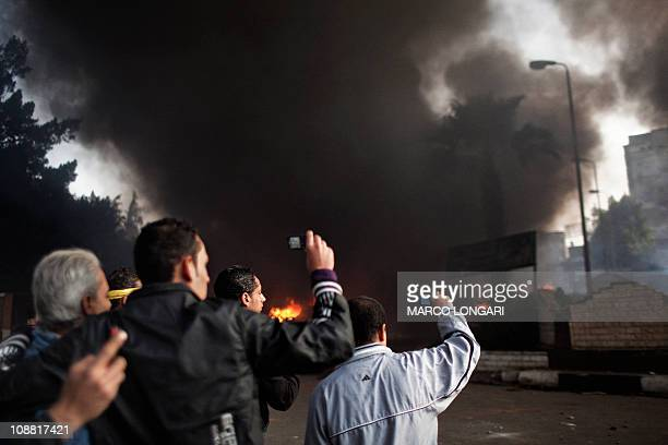 Egyptians take pictures with their cellphones of a burning police station set ablaze by rioters near the Sultan Hassan alRifai mosque in central...