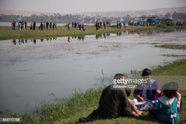 Egyptians walk and picnic along one of the branches of the Nile in the southern town of Mallawi on April 9 as they celebrate Sham alNessim a...