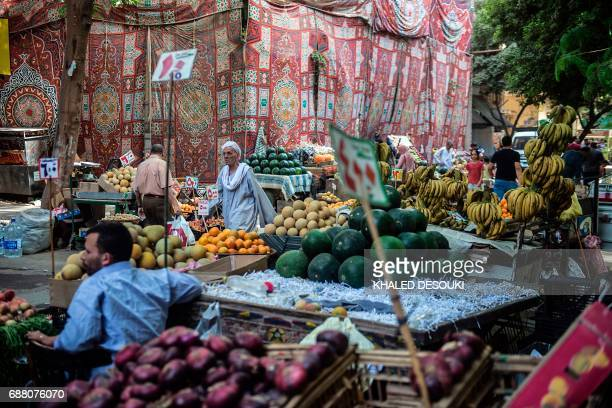 Egyptians walk at a market in the Egyptian capital Cairo on May 15 2017 Ramadan is a time for daytime fasting and lavish evening feasts but Egyptians...