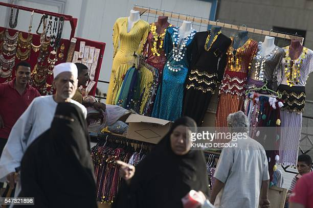 Egyptians walk past a street vendor selling traditional dresses near alAzhar mosque in Cairo on July 14 2016 Many believed that Mohamed Morsi's...