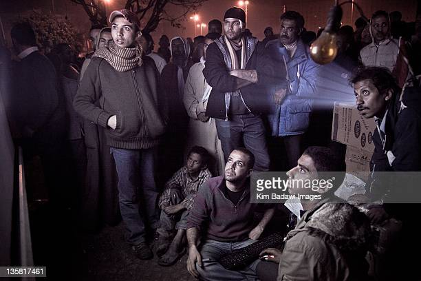 Egyptians watch online Facebook projections at night on February 6 2011 in Tahrir Square in downtown Cairo Egypt