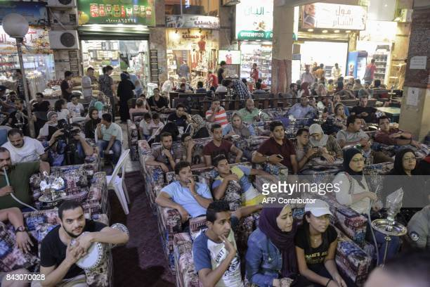 Egyptians watch the FIFA World Cup 2018 qualification football match between Egypt and Uganda at a café in Cairo's 6th of October City west of the...