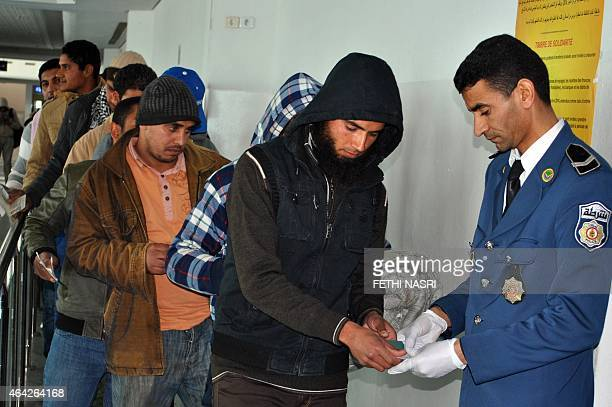 Egyptians who were formerly residing in Libya have their documents checked by Tunisian customs at Djerba airport on the TunisianLibyan border before...