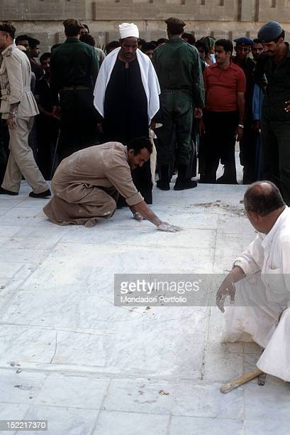 Egyptians workers cement with hands interstices of slab marble that cover the grave of Sadat President in the mausoleum of the unknown soldier...