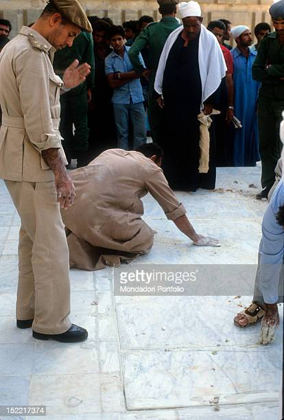 Egyptians workers helped by soldiers cement with hands interstices of slab marble that cover the grave of Sadat President in the mausoleum of the...
