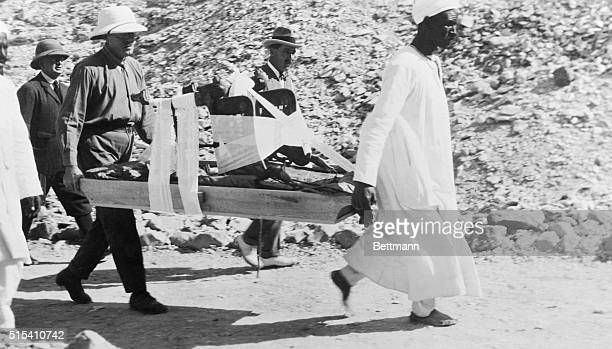 Egyptologist Howard Carter watches as porters carry a throne from King Tutankhamen's Tomb in the Valley of the Kings in Egypt The throne is inlayed...