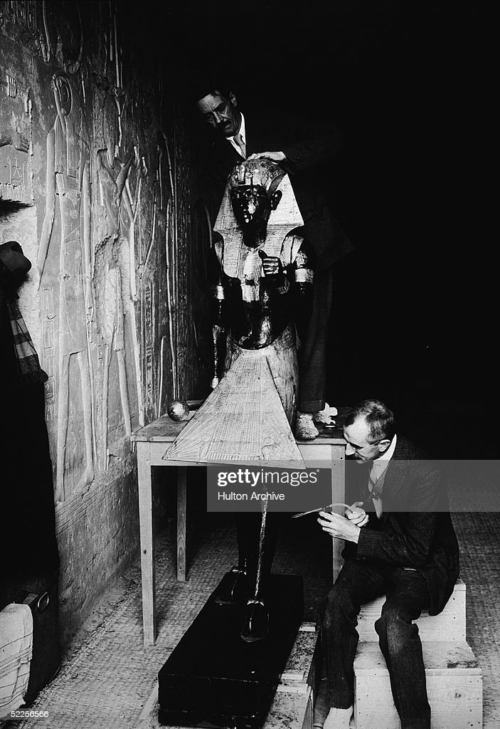 Egyptologists on Howard Carter's team, American Arthur Mace (1874 - 1928) of the Metropolitan Museum and British chemist Alfred Lucas (1867 - 1945) of the Egyptian government, examine a life-size statue of Pharaoh Tutankhamen, better known as King Tut, Valley of the Kings, Thebes, Egypt, 1923.