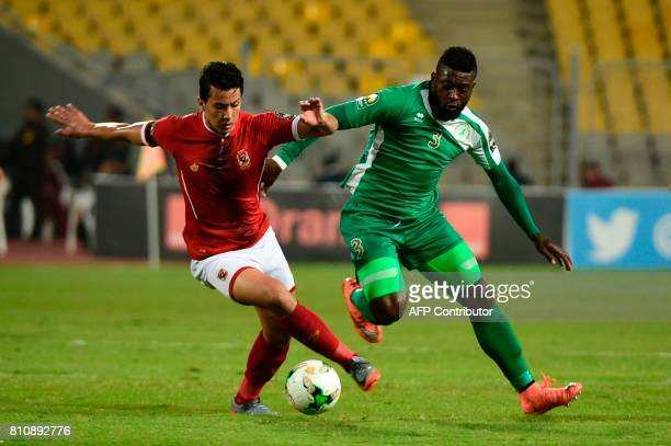 Egypt's Al Ahly footballer Amr Gamal vies for the ball with Cameroon's Cotonsport player Paul Serge during their African Champions League group stage...