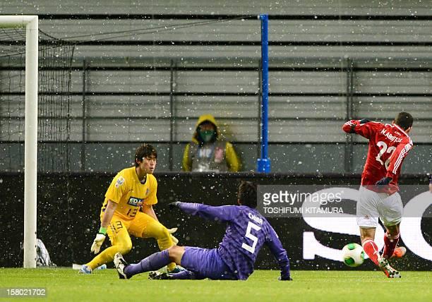 Egypt's AlAhly forward Mohamed Aboutrika shoots to score a goal past Japan's San Frecce goalkeeper Takuya Masuda and defender Kazuhiko Chiba during...