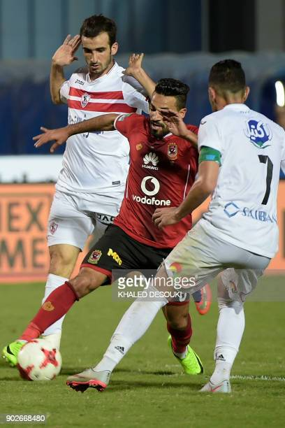 Egypts alAhly player Islam Moharb fights for the ball against Zamalek's Mahmoud Abdelaty and Hazem Immam during the the Egyptian Premier League...