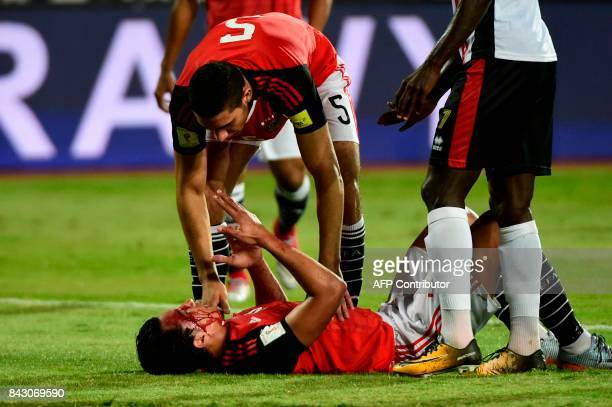 Egypts Amr Gamal reacts on the ground after he was injured during the FIFA World Cup 2018 qualification football matchh between Egypt and Uganda at...