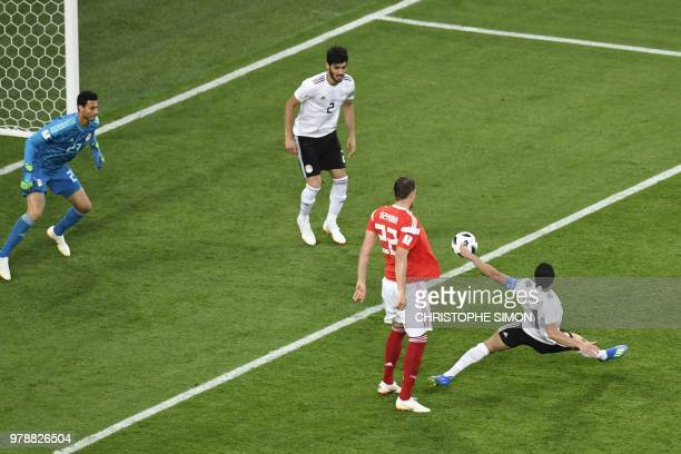 Egypt's defender Ahmed Fathi deflects the ball into his own net during the Russia 2018 World Cup Group A football match between Russia and Egypt at...
