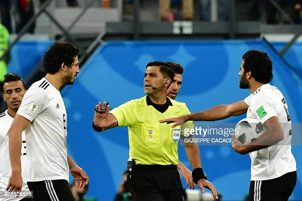 Egypt's defender Ahmed Hegazi and Egypt's forward Marwan Mohsen argue with referee Enrique Caceres from Argentina during the Russia 2018 World Cup...