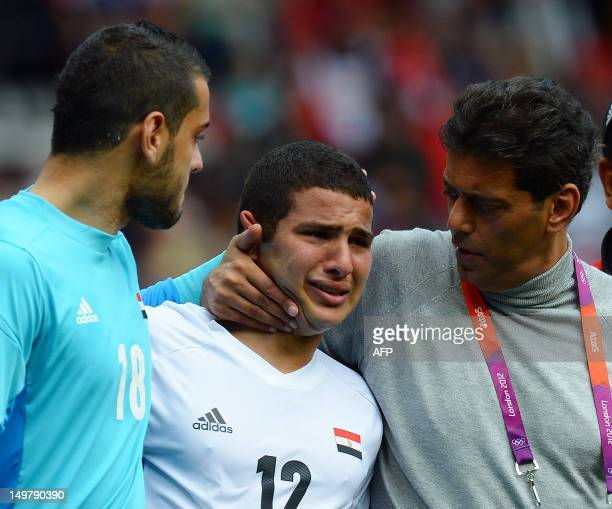 Egypt's defender Islam Ramadan is consoled by Egypt's coach Hani Ramzi and Egypt's goalkeeper Bassam Mohammed after the London 2012 Olympic Games...